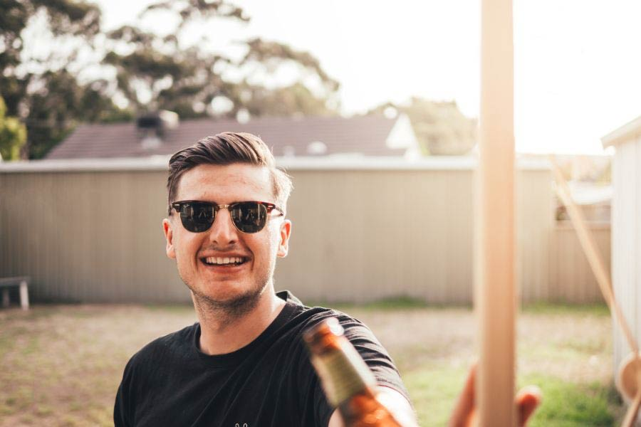 Young man in sunglasses sitting at a picnic table with friends